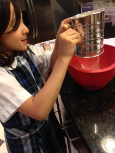 Audrey my boo boo sifting the sugar and almond flour